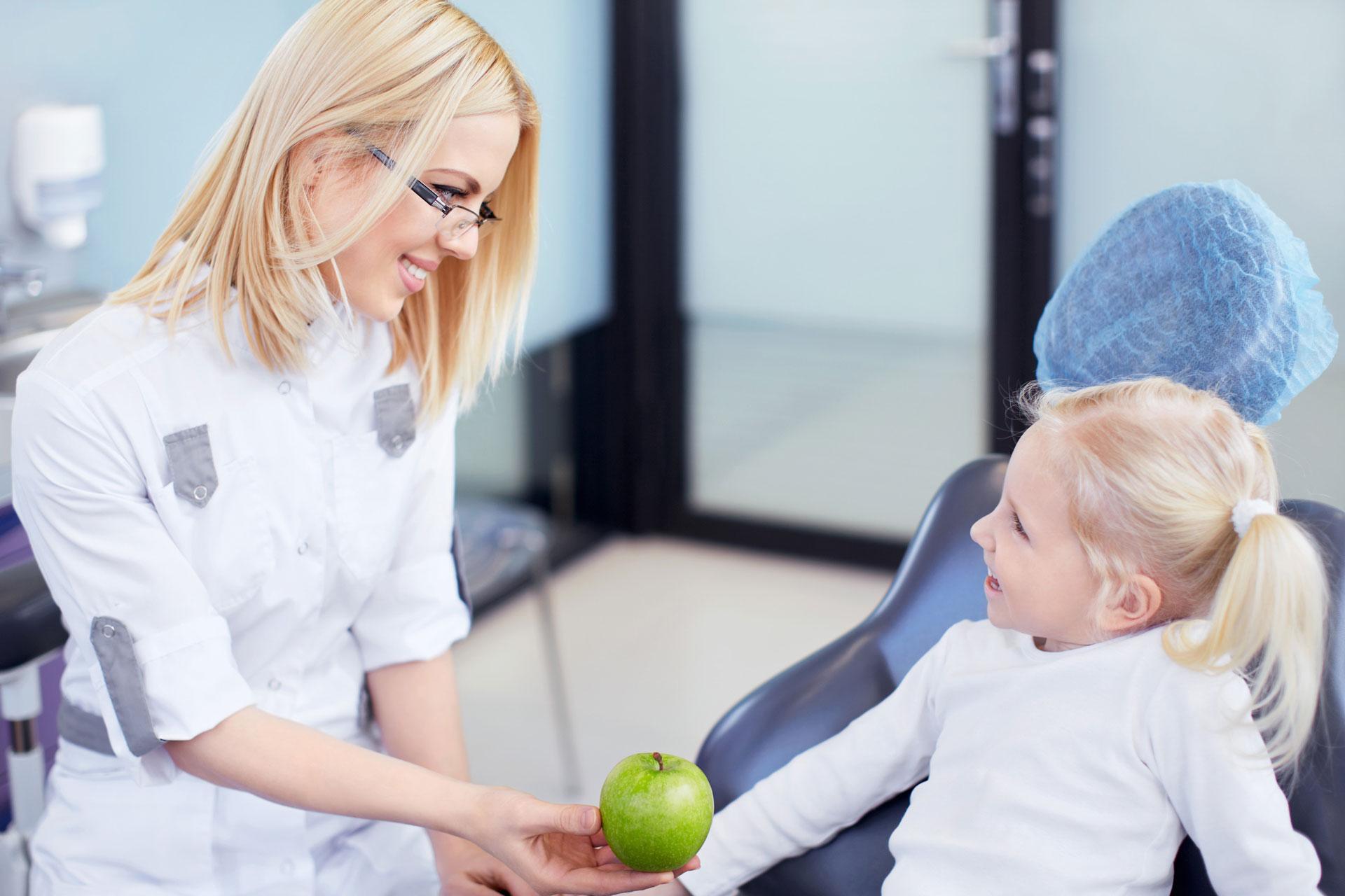 Dentysta podaje jabłko dziecku